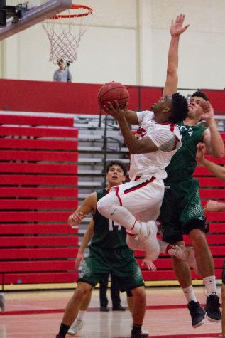 City College Vaquero Drayton Howell (No. 12) attempts to regain the lead in the first half of the game against the Cuesta Cougars on Saturday, Feb. 4 in the Sports Pavilion. The game went into double overtime.