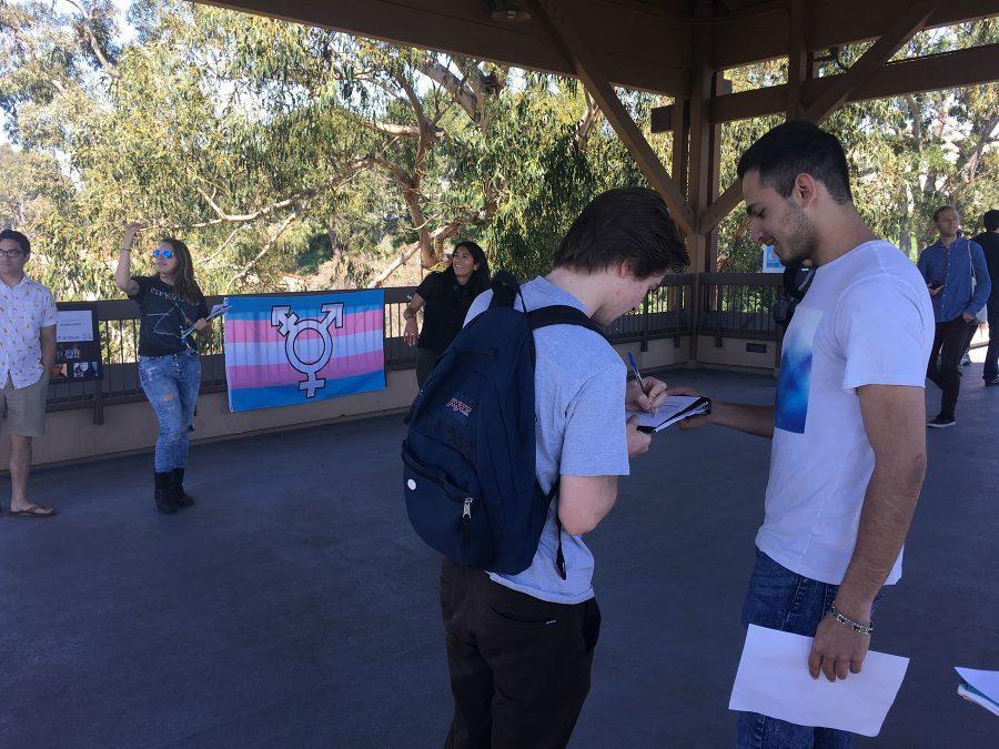 City+College+Student+Thomas+Crane+signs+a+petition+supporting+gender+neutral+bathrooms+on+campus+from+David+Panbehchi%2C+commissioner+of+events+for+the+Student+Government%2C+on+Thursday%2C+March%2C+16%2C+on+the+bridge+between+East+and+West+campus.+The+rally+spread+awareness+and+promoted+gender+inclusivity.%0A