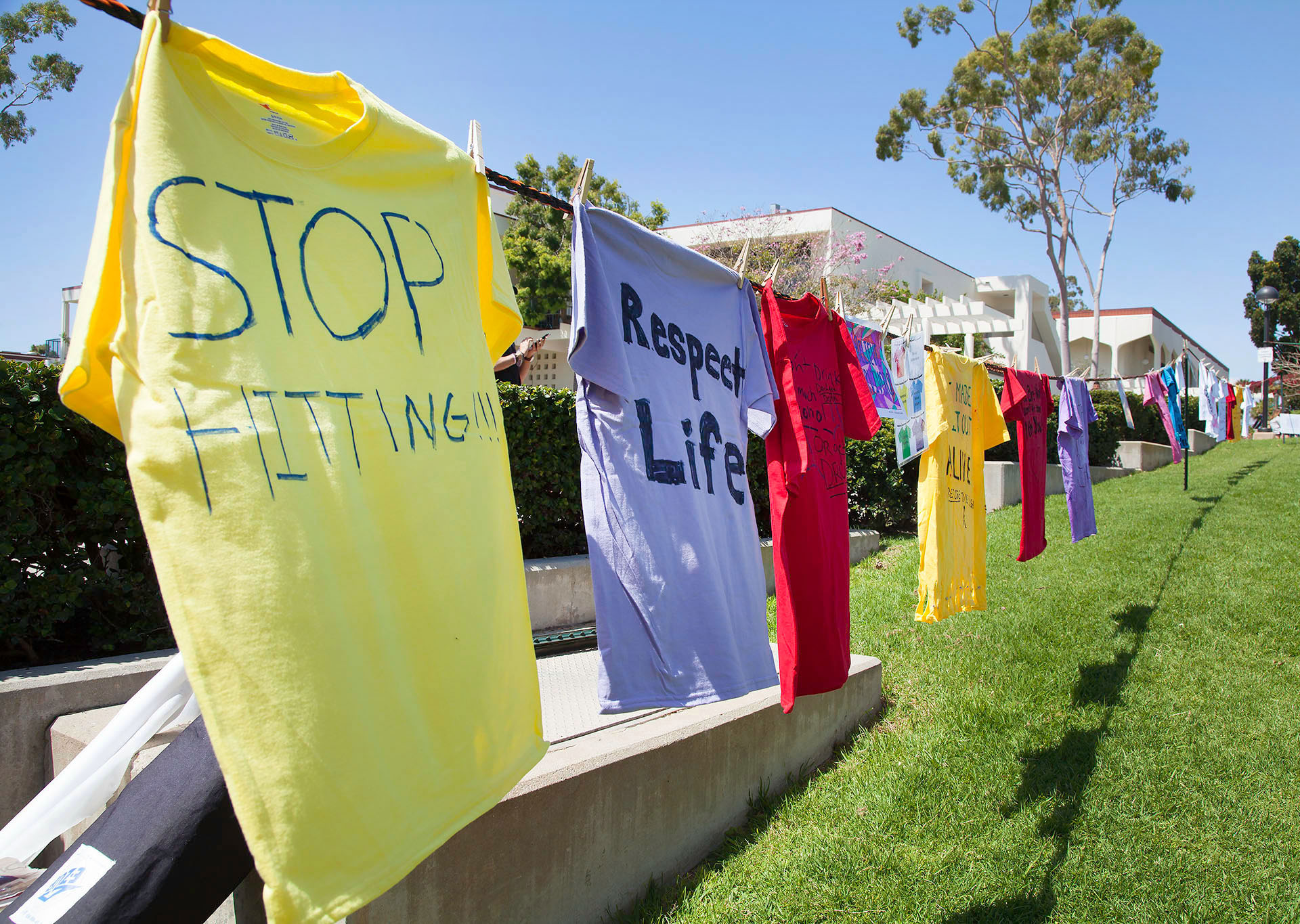 Different colored shirts that students have written on for the Clothesline Project on April 12, at the Friendship Plaza at City College. At the event, students made different colored shirts to tell their story. A red shirt symbolizes rape, a yellow shirt symbolizes domestic violence, and a purple shirt stands for physical or sexual abuse against the LGBT+ community.