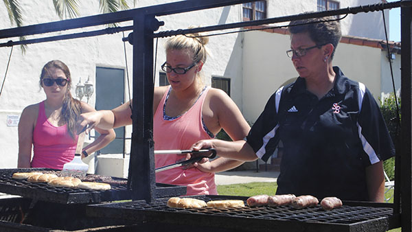 Dr. Paula Congleton flips the burgers with help from Sabine Bourret, while Sashia Pelaez looks on during a barbaque at the Veterans Memorial Building on Friday, Sept. 13, 2013, in Santa Barbara, Calif.