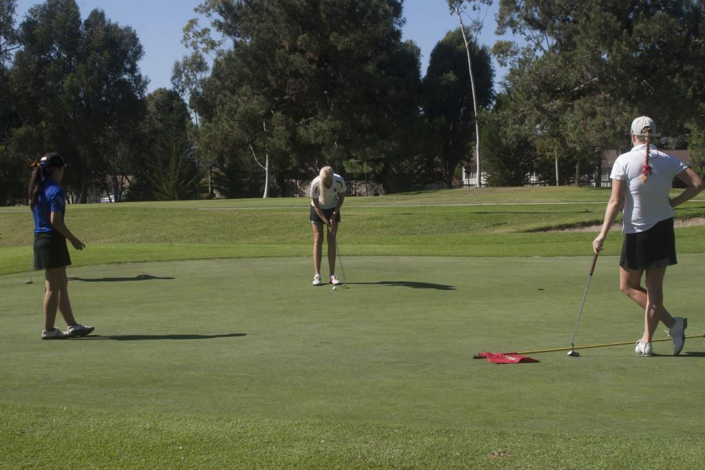 Paramee Suwantanma (left, Citrus College) and Kendall Huser (right, Bakersfield College) watch how Fanny Johansson (Santa Barbara City College) tries to make a hole at the golf invitation at the Santa Barbara Golf Club, Santa Barbara (Calif.), at oktober 14, 2013.