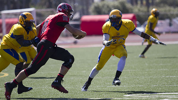 Vaqueros quarterback Joshua Martin (No.10) runs the ball passed LA Southwest linebacker Tim Lucious (No.32) to gain yards in the Oct. 5, 2013 conference matchup.