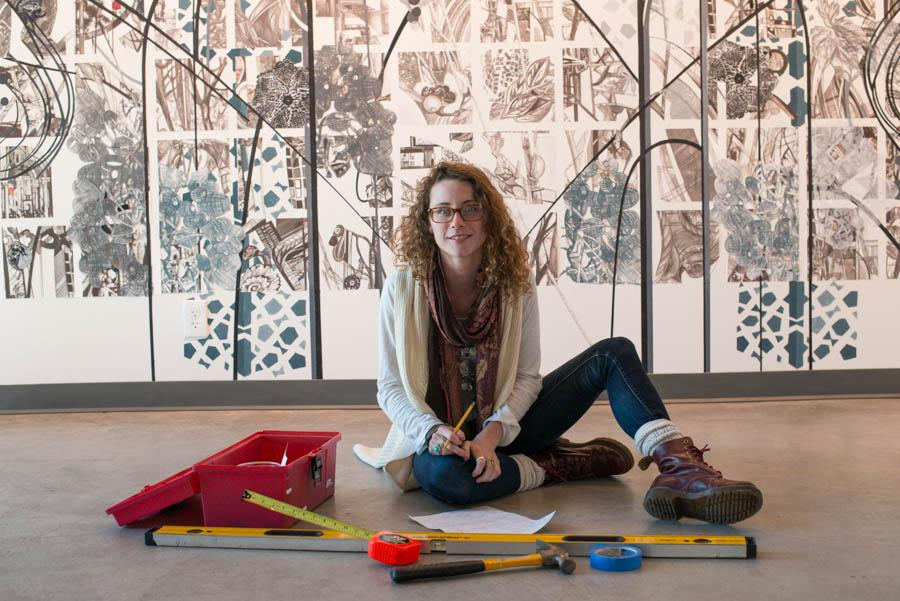 Art Intern, Lia DeWit, 22,  works in the Atkinson Gallery on her first curated exhibit,