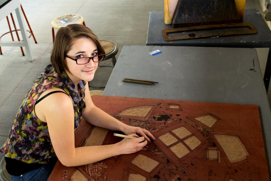 Sasha Colbert, carving up her latest woodwork creation on Feb. 20, in the Humanities Building Print Making Lab at City College.