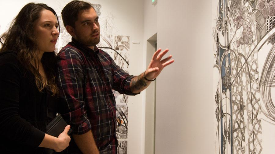 City College students Ian King and Rebecca Estrada, discuss the details of Ann Diener's new artwork on display on Friday, Jan. 31, in City College's Atkinson Gallery.