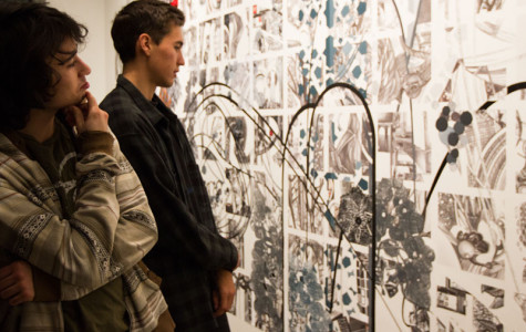 """From left, City College students Rory Fearon and JJ Osterman examine the new art on Friday Jan. 31, at the Atkinson Gallery. """"I can see the beauty in chaos,"""" said Fearon."""