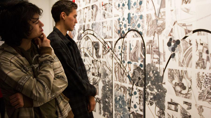 "From left, City College students Rory Fearon and JJ Osterman examine the new art on Friday Jan. 31, at the Atkinson Gallery. ""I can see the beauty in chaos,"" said Fearon."