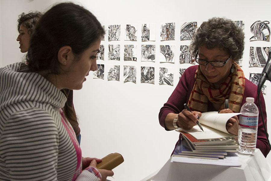 Lynne Thompson, (right) signs her book for communication major, Eranush Mkrtchyan, 21, in the Atkinson Gallery at City College. Thompson is the author of the two poetry books