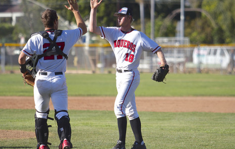 Catcher Patrick O'Brien (No. 27) high-fives pitcher Kit Larson (No. 18) after getting the final out in a win against Oxnard College on Tuesday, March 18, at Pershing Park in Santa Barbara. Larson pitched the last two innings of the game en route to a 4-2 Vaqueros victory.