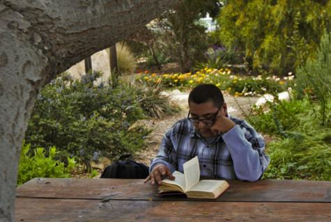 """City College student, Antonio Gomez, reads the book """"Killer Joe"""" by Tracy Letts at the Chumash Point on Friday, 25 April. """"If you really wanna go to a peaceful place, this is the spot,"""" Gomez said. Photo by Catalina Avila."""