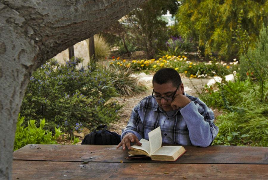City College student, Antonio Gomez, reads the book Killer Joe by Tracy Letts at the Chumash Point on Friday, 25 April. If you really wanna go to a peaceful place, this is the spot, Gomez said.