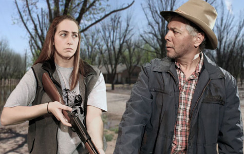 A woman with a gun stares at a man with a hat who stares back with a confused look on his face.