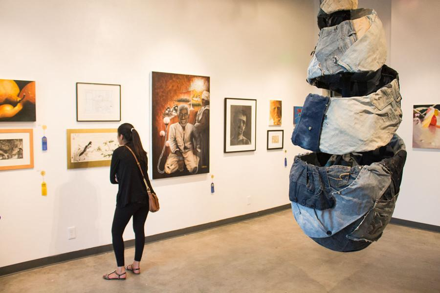 Jose Solis sculpture entitled Bound to Denim suspends from the ceiling as attendees of the Annual Student Exhibition exit on Friday, April 25, in the Atkinson Gallery at City College. Solis sculpture is comprised of denim, buttons and zippers with an asking price of $10,000.