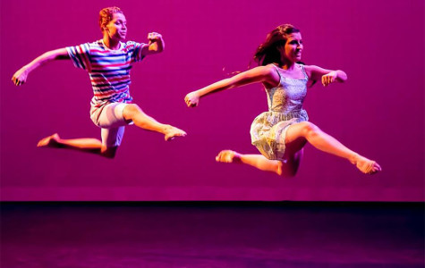 Two dancers leap across a stage.