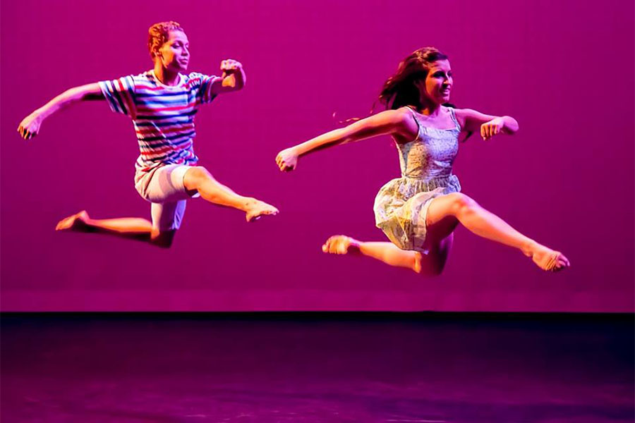 Two+dancers+leap+across+a+stage.