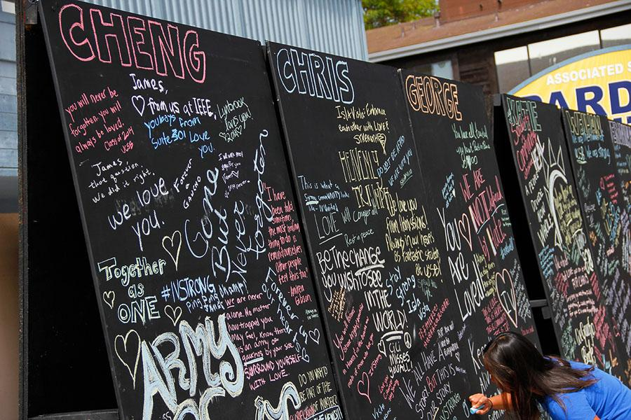 A woman writes with chalk on the Art Wall of Remembrance at 6550 Pardall Street, Isla Vista, on May 27.