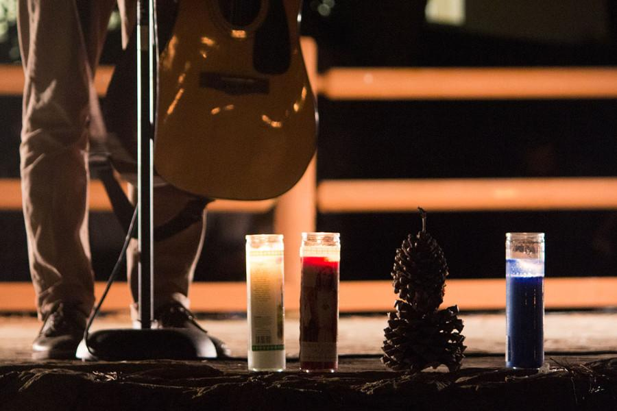 A man offered his condolences by playing Lean On Me, made famous by Bill Withers, during the candlelight vigil on Saturday, May 24, 2014, at Anisqovo Park in Isla Vista, Calif.