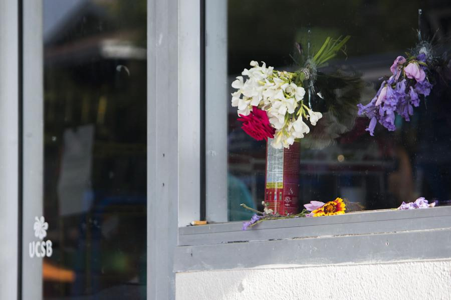 Flowers rest in bullet holes from Elliot Rodger's rampage at IV Deli Mart on Saturday, May 24, on Pardall Road in Isla Vista, Calif. UCSB student, Christopher Martinez, 20, was shot by Rodger in front of the market Friday night. Since then, Isla Vista residents have created memorials at various crime scenes.