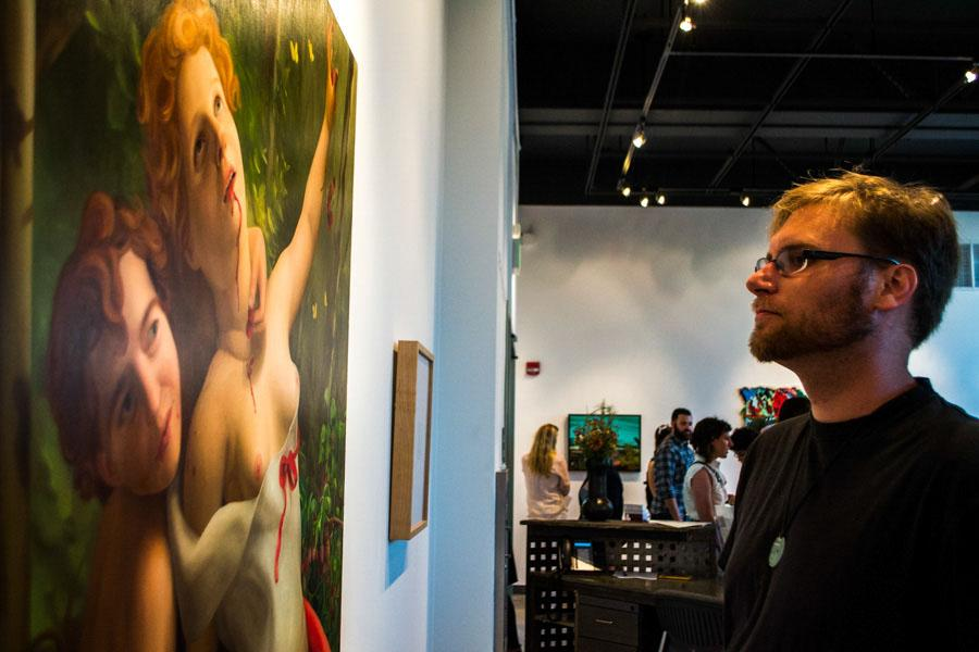 City College student Byron Blanco observes Laura Krifkas oil painting, Lambs, featured in this years Art Faculty Biennial exhibit hosted by the Atkinson Gallery on Friday, August 29. The piece, priced at $800, was created this year and will be on display through Sept. 26.