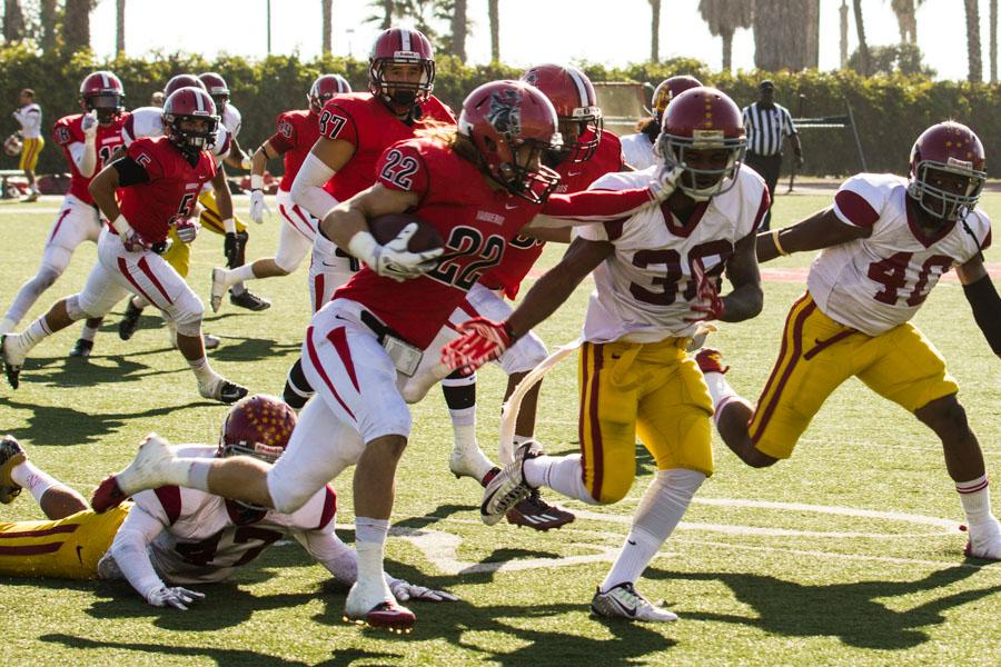 Vaquero wide receiver and kick returner Tyler Higby (No. 22) stiff-arms Glendale's starting linebacker Chris Riley (No. 33) on a kick return in the beginning of City Colleges game against Glendale Community College Nov. 15, in Santa Barbara at La Playa Stadium.