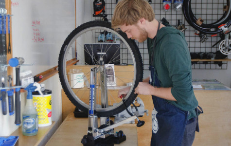Student worker Kevin McClintock works on straightening a student's wheel at the new Bici Centro station, Wednesday, Feb. 18, located on the East Campus Bridge entrance at City College. This new do-it-yourself bike shop is open from 10 a.m. to 2 p.m. Monday through Thursday.