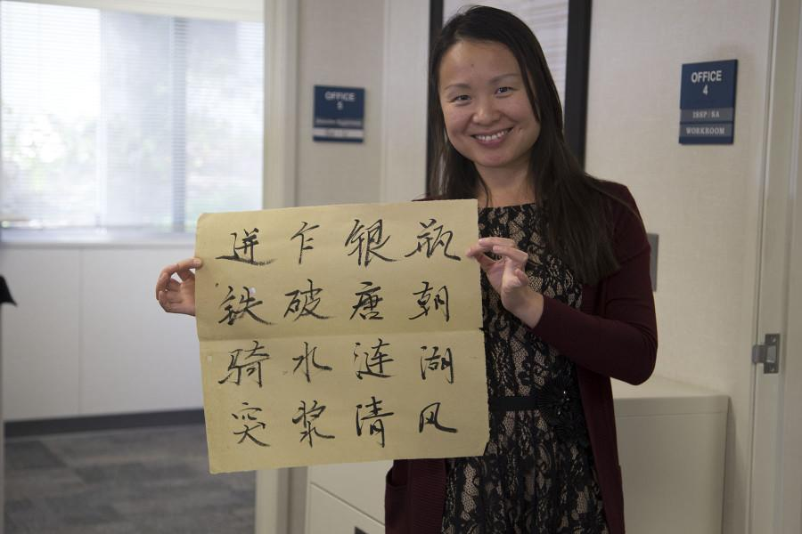 Yan Service, admission coordinator and club adviser for the Chinese Scholars and Student Association, holds up a calligraphy piece made by student Cheng Chen, Thursday, Feb. 19, in the International Student Services Building on City College's East Campus.