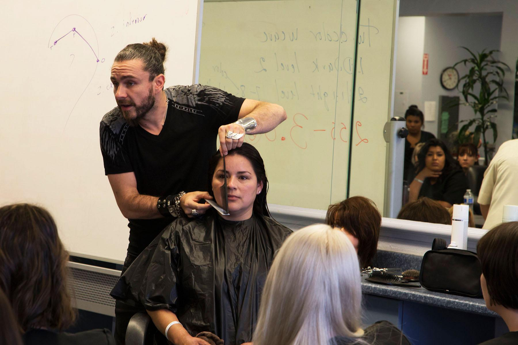 Raphael Perrier, a prominent hair stylist, demonstrates his hair cutting techniques on model Margarita Perez, a student in the cosmetology program, Tuesday, April 21, at the Cosmetology Academy in the Magnolia Shopping Center in Goleta. 'The most important part of a haircut is all the geometrics,' says Perrier.