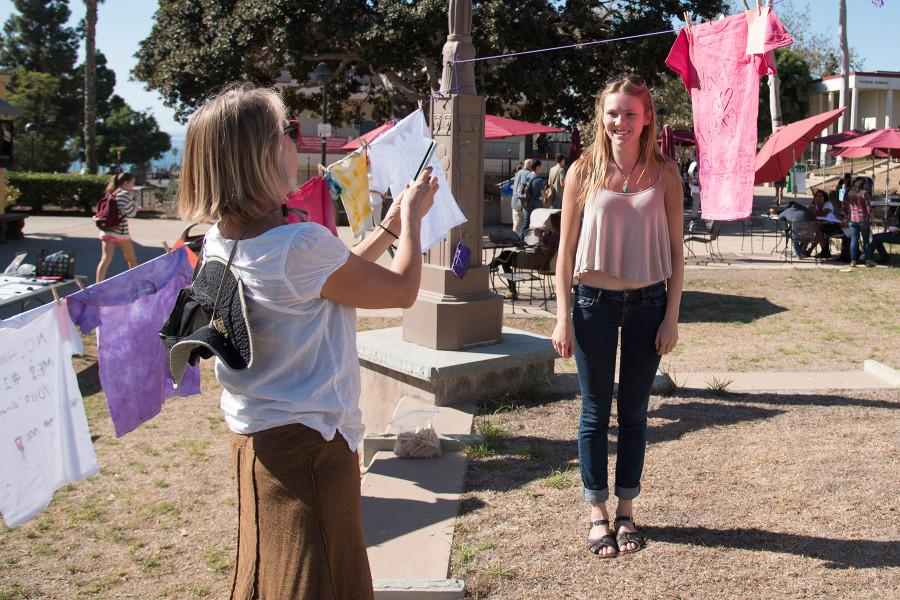 Betsy Phillips (left), bilingual counselor for the student health department, takes time to record the creation of City College student Julia Dyer who has just hung her t-shirt stating 'Never a Victim' for the SBCC 2015 Clothesline Project, Monday morning, Oct. 26, in the Friendship Plaza at City College. The Clothesline Project is an effort to raise awareness about sexual violence and is presented by Student Health and Wellness and City College Connect, with participation from the Feminist Club, the Rape Crisis Center, the Health and Wellness Center and the Pacific Pride Foundation.