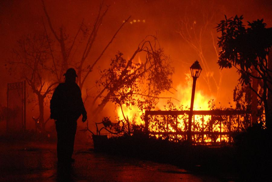 A Los Angeles City Firefighter surveys the fire damage on Camino Alto just after midnight on Friday, Nov. 14, 2008, in Santa Barbara. Fire crews from all over the state came to assist in firefighting efforts during the Tea Fire.