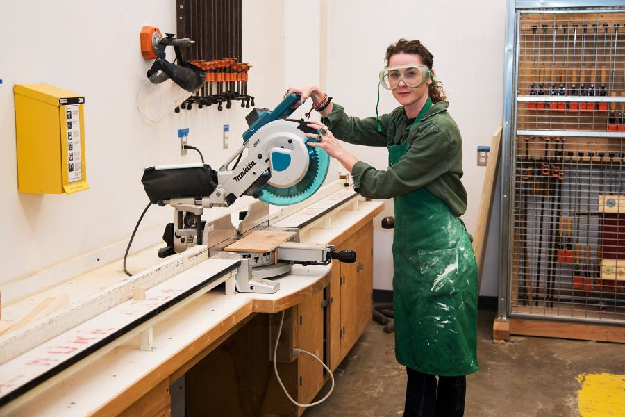 Art history major Lia DeWitt poses with a cut-off saw she uses for artwork creations, Friday, Nov. 20, in the woodshop of the Humanities Building at Santa Barbara City College. With a bachelor's degree in art, DeWitt plans to extend her credentials as an art teacher or museum curator.