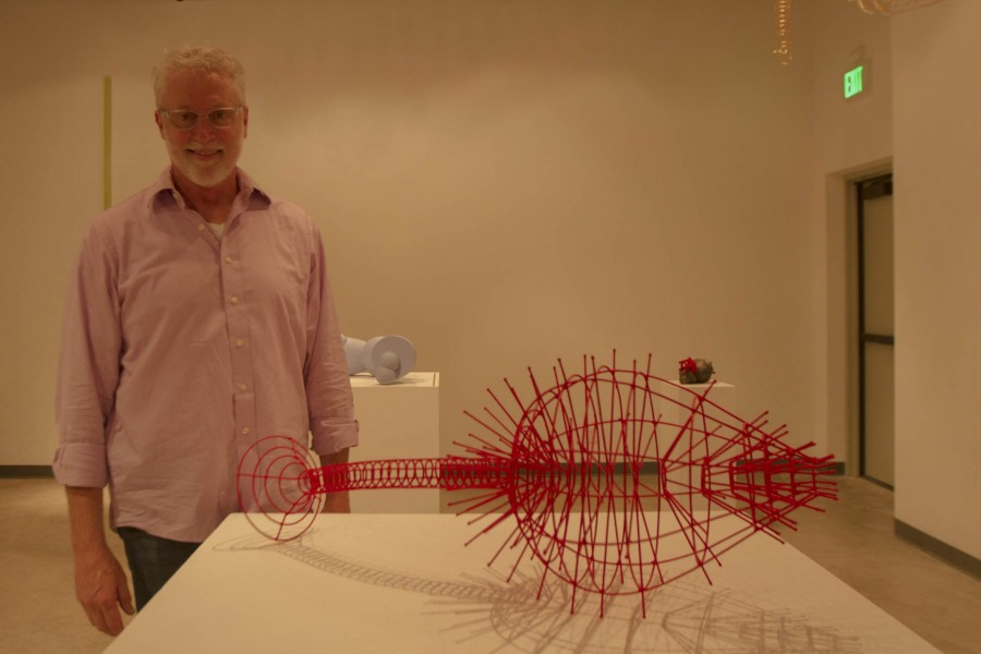 Edward Ink, 3D Design and Sculpture Professor, poses in front of one of his sculptures at his retirement open art exhibit