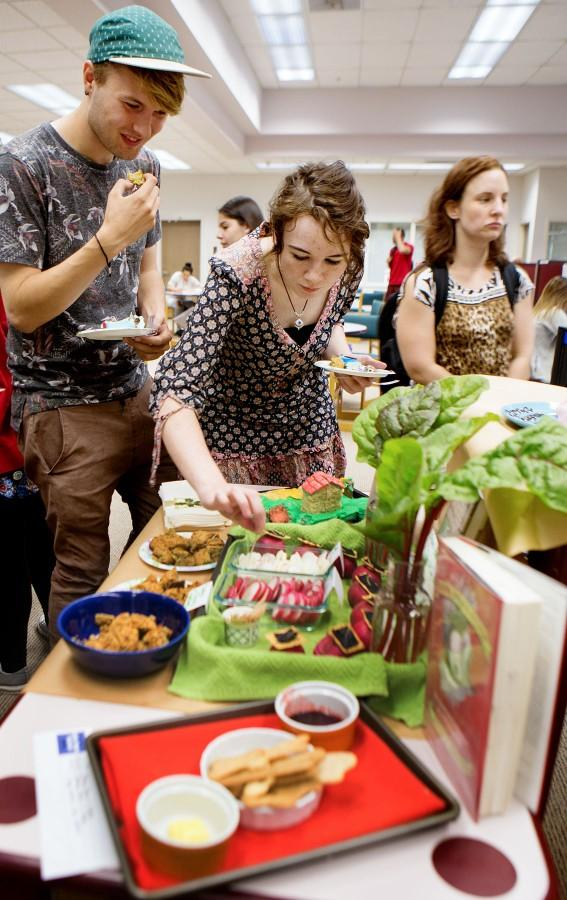 Graphic design major Brendan Sugrue, 20, stands with environmental studies student Bella Strid, 22 while she goes for a radish on one of the more healthier options at the 6th Edible Book Festival on Wednesday afternoon, March 23, in City College's Luria Library.