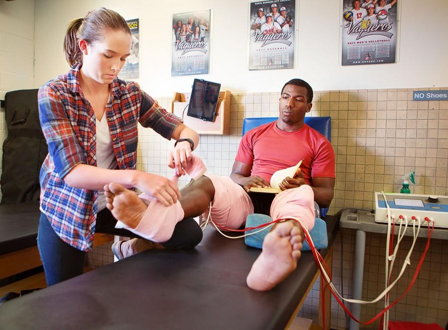 Danielle Barkey places therapeutic electrodes on Deshawn Phelps, track and field sprinter, on Thursday, March 11, at the City College Athletic Training Center in Santa Barbara, Calif. Barkley is enrolled in PE 290, a class which enables students to try out different jobs in their field in exchange for four transferrable units.