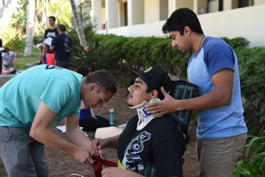 EMT students, from left, Cody Thompson, 21, Paco Pulido, 22, and Varun Battu, 20, practice putting an immobilization device on each other during their lab on Thursday, March 24, at City College. Two of the course coordinators may be stepping down after this season.