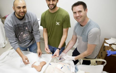 Male nursing students (From Left) Rogelio Tafoya, Tyler Lawrence, and Skyler Lyon practice changing complex abdominal wound dressings and administering medication through central lines on a practice mannequin Thursday morning, April 21, in the Health Technology Building room 277 at Santa Barbara City College, Santa Barbara. These nurses are a few of the members in the Men in Nursing club at City College.