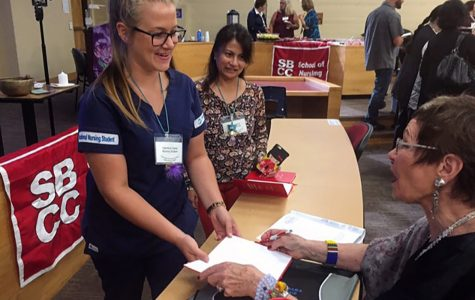 Nursing student Harmony Dante receives an autograph from Dr. Jean Watson before her introduction Friday, Sept. 16, in the City College Administration Building. Watson, who is a renowned educator in nursing, came to City College to talk to nursing students and staff about the importance of compassion in the profession.