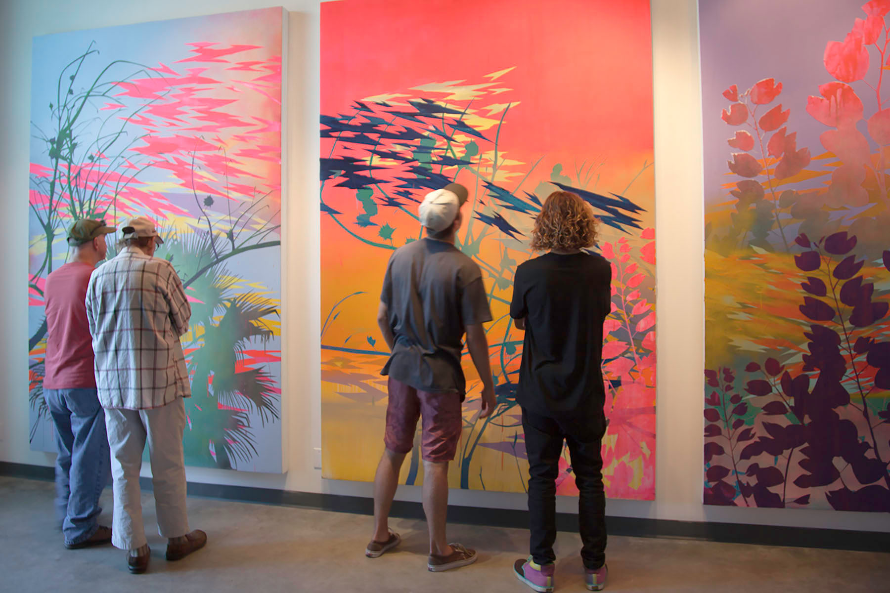 Art goers admire the work of Devon Tsuno on Friday, Sept. 16, at the Atkinson Gallery. Tsuno's gallery consists of abstract landscape paintings that focus on Los Angeles' bodies of water and native vs. non-native vegetation.