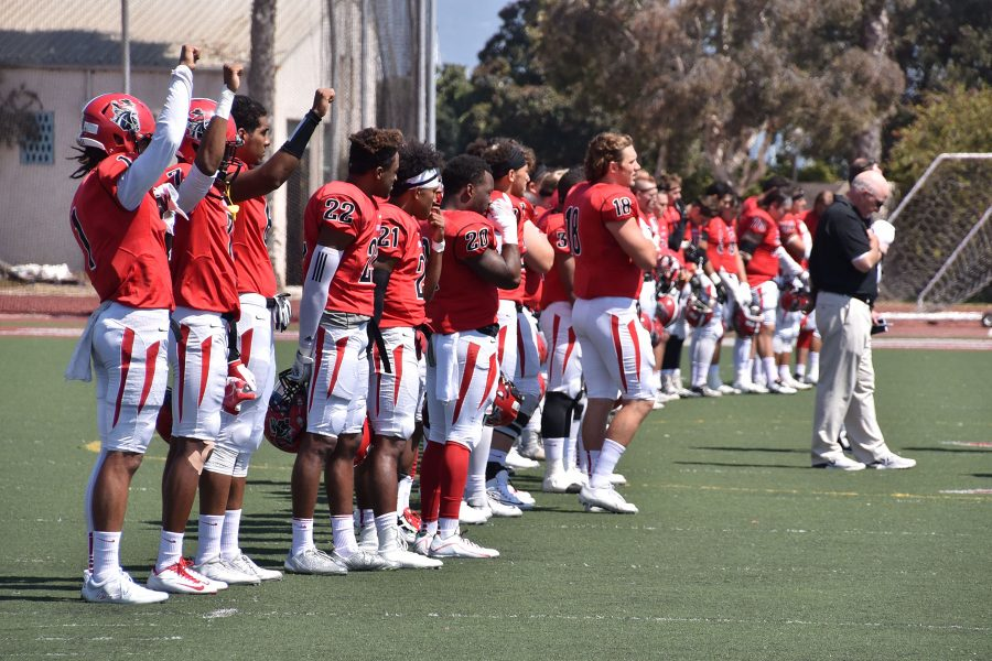 City College football players (From left) Elijah Cunningham (No. 1), Donald Lambert (No. 7) and Jonathan Licea (No. 6) stand in solidarity with NFL player Colin Kaepernick during the national anthem at the football game against South West Los Angeles on Saturday, Sept. 17, at La Playa Stadium. of African Americans.