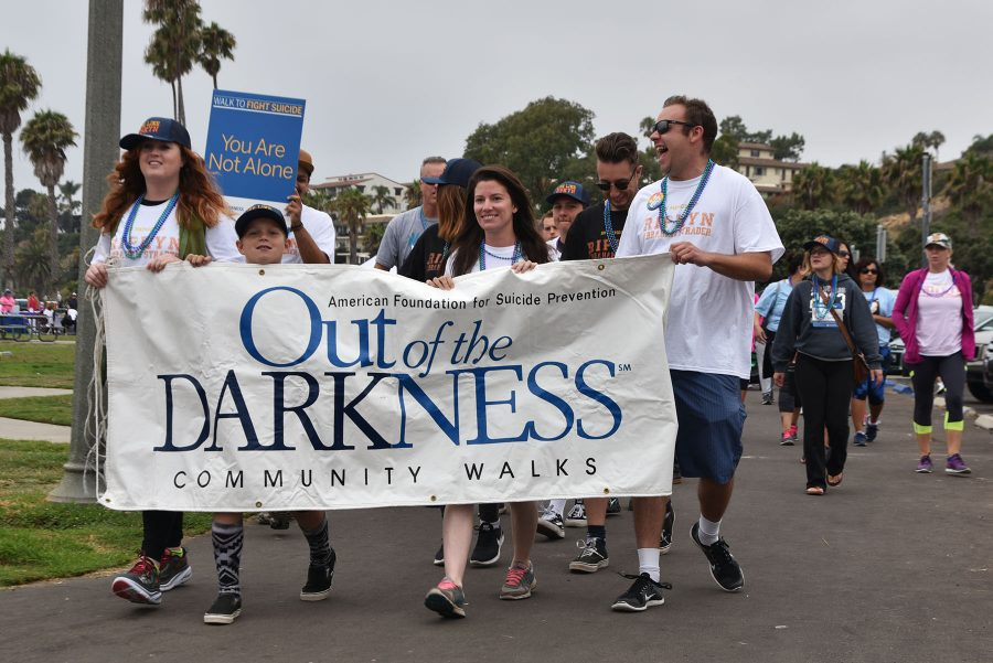 The suicide prevention banner is carried by (from left) Polly Davidson, Makai Callis, Brooke Cuevas and Orion Brutoco during the community walk on Sunday, Sept. 11, on Leadbetter Beach in Santa Barbara. The four were walking in remembrance of Ripkyn Strader, a previous City College student, who passed away on Aug. 16, 2016 from suicide.