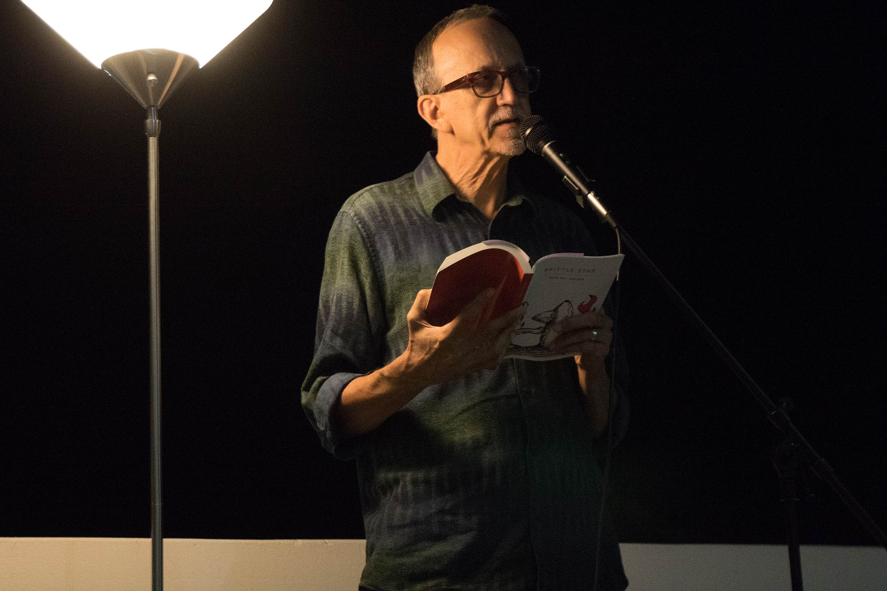 """Rod Val Moore, author and member of What Books Press, reads an excerpt from his novel """"Brittle Star"""" at a collective reading performance on Thursday, Oct. 20, on the balcony of the Atkinson Gallery. City College's creative writing department and Gunpowder Press sponsored the reading."""