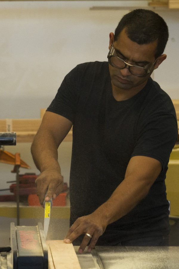 Armando Ramos demonstrates how to split wood with a table saw on Monday, Oct. 3, in his Humanities building lab at City College. Ramos is the new arts instructor who specializes in 3D sculptures made from all different types of material, including wood and cardboard.