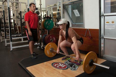 Diego Santana Ramirez instructs Hannah Arnold, 19, how to correctly do dead lifts on Oct. 19, in the Life Fitness Center at City College.