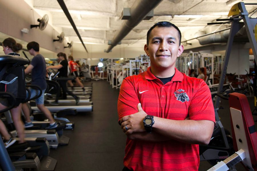 Diego Santana-Ramirez stands in front of exercise equipment on Wednesday, Oct. 19, in the Life Fitness Center at City College. Ramirez is the first full-time lab-teaching assistant hired in the Life Fitness Center and his duties include working with students to help them develop their training routine.