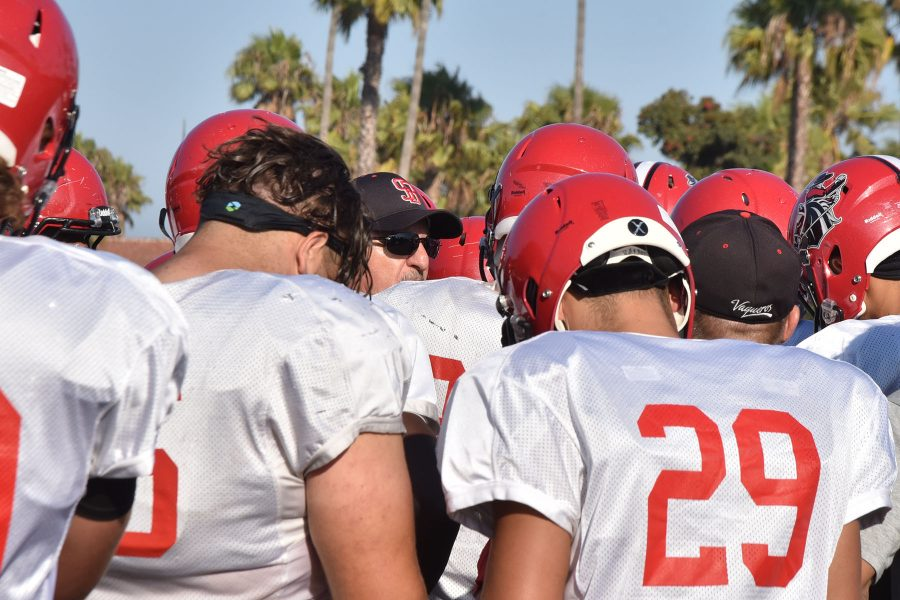 Craig Moropoulos (center), City College head football coach, discuses tactics with the offence on Monday, Aug. 29, at La Playa Stadium. This is Moropoulos' 10th year as the head football coach and has led the team to a 5-2 record so far this season.