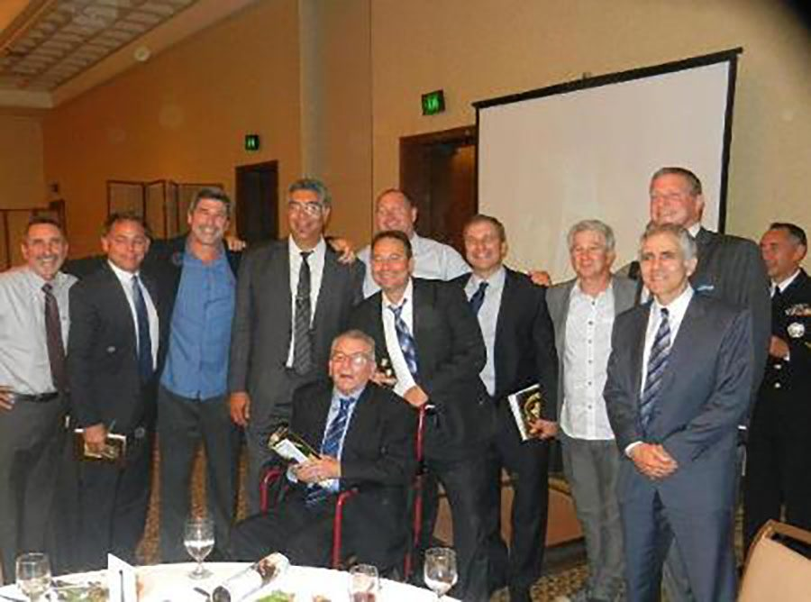 Coach+Frank+Carbajal+seated+in+front+of+some+of+his+former+players.