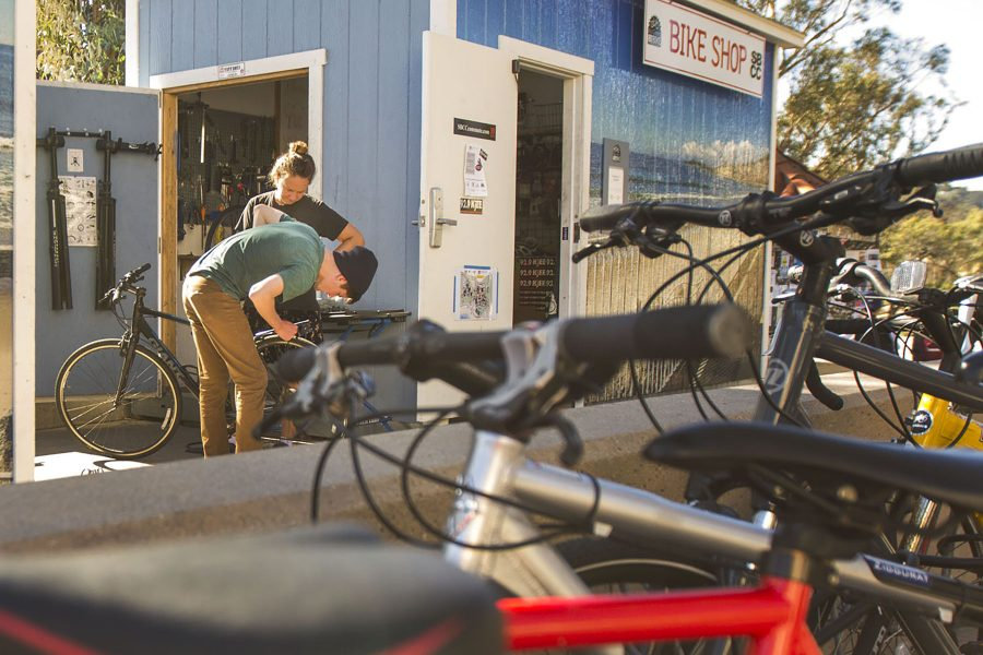Lynneal Williams, mechanic for the Campus Bike Shop, helps mechanical engineering student Alex Reichmayr with his rear brake cables on Thursday, Nov. 10, at the City College Campus Bike Shop. The shop is a satellite location of Bici Centro, where Williams also works.