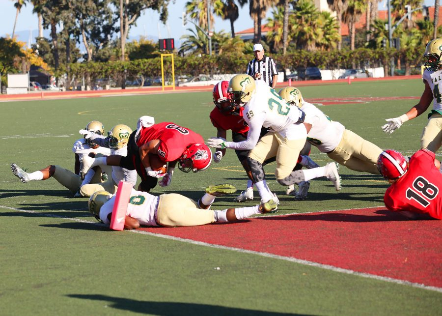 Sophomore Cedric Cooper (No.9) jumps over a heap of defenders in the third quarter for a touchdown against LA Valley on Nov. 12, at City College's La Playa Stadium. City College lost to LA Valley, 47-35.
