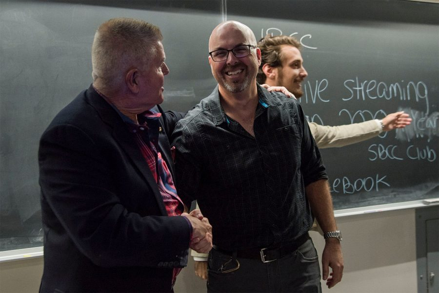 Philosophy Instructor Mark McIntire (left) shakes hands with Biological Sciences Associate Professor Adam Green after their debate about climate change put on by 2020 A Year Without War on Wednesday, Nov. 16, at City College. The two agreed on several points regarding climate change but differed on how to fix the problem.