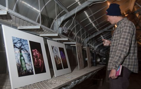 English major Cole Waldron walks through the exhibition looking at all the student works of art on Tuesday, Nov. 29, City College East Campus green house. The student art exhibition was called