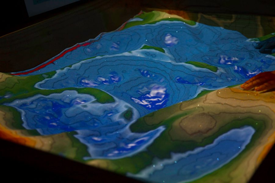 Children playing in the augmented reality sandbox on Saturday, March 18, in the Earth and Biological Science Building. The augmented reality sandbox maps the topography of the sand box in real time by using a projector and an Xbox Kinect.